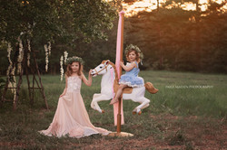 two sisters on a carousel horse