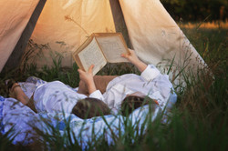 brother reading in a tent together