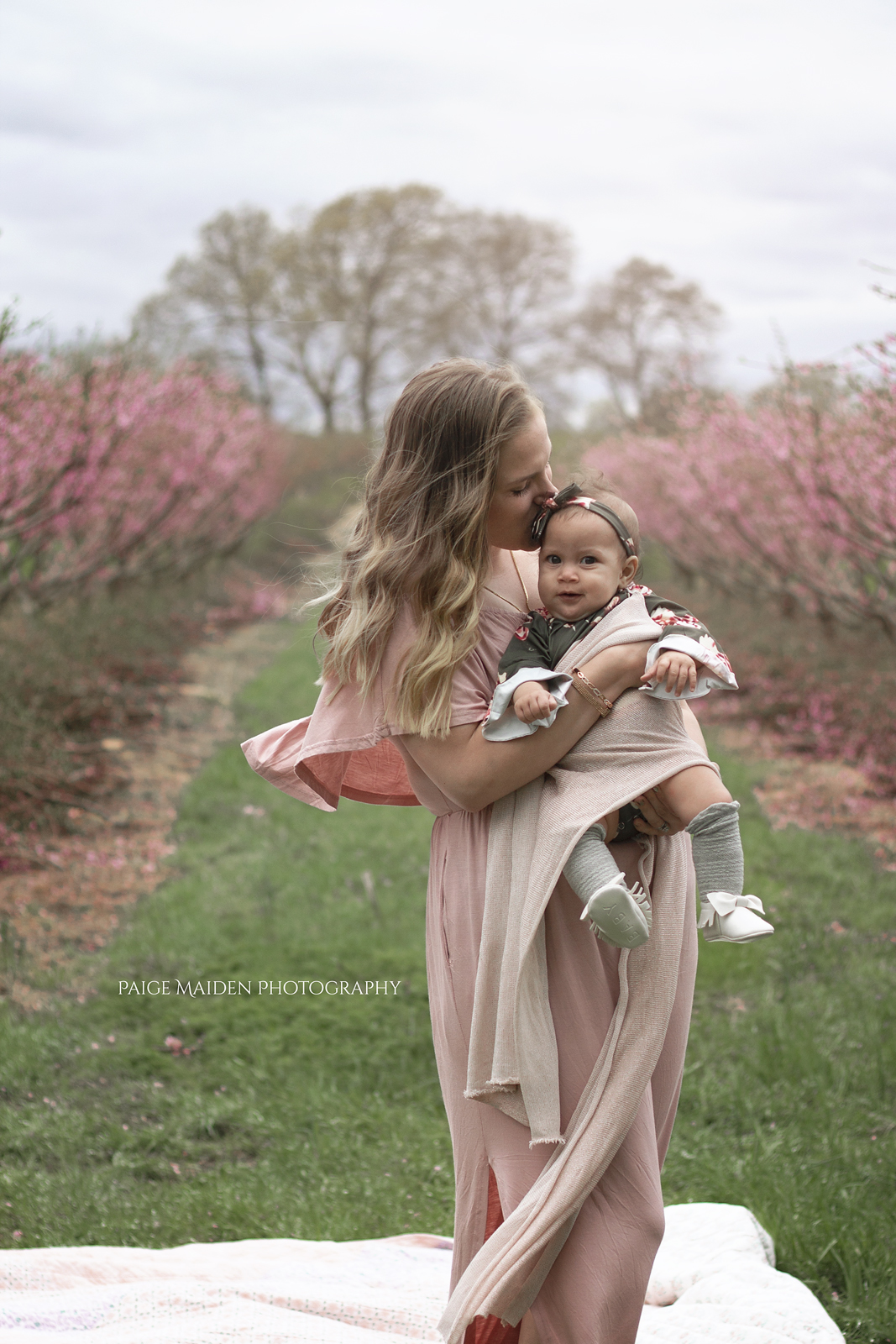 mom kissing baby girl in peach trees