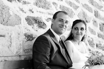 la mariée regarde le marié assis contre un mur en pierre