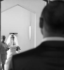 arrivée de la mariée accompagnée de sa mère à l'église en arrière plan. le marié la regarde arriver en premier plan en noir et blanc