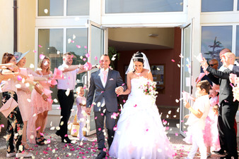 La sortie de l'église, les mariés main  dans la main sortent sous une pluie de pétale de fleurs roses et blanches