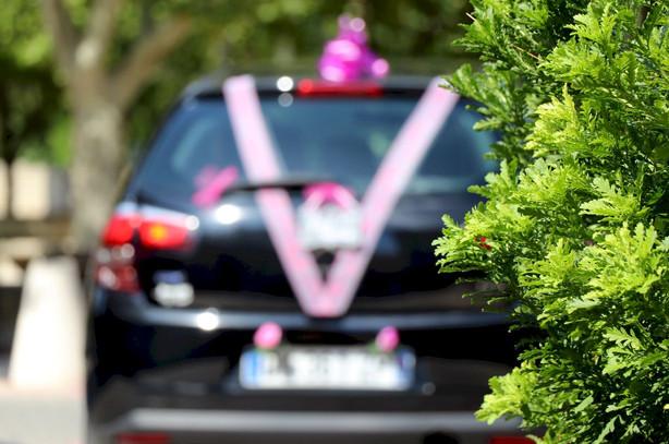 voiture des mariés décorée de rubans roses