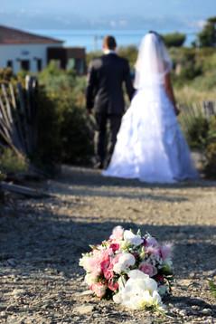 le bouquet de fleur de la mariée par terre en premier plan avec les mariés de dos en arrière plan