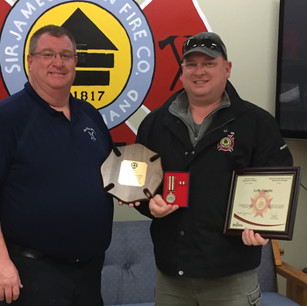 Firefighter Scott Haughn receiving his 25 year provincial medal for his dedication to the St. Andrews Fire Department. From L to R: Chief Kevin Theriault and Firefighter Scott Haughn