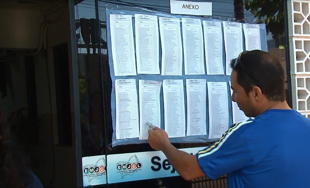 Pai procura nome de filho na lista de alunos de escola