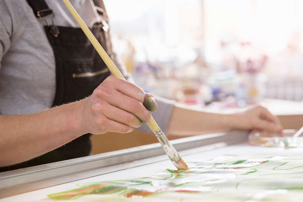 woman using an artist' paint brush to paint