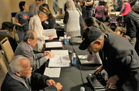 Veterans sign books for guests