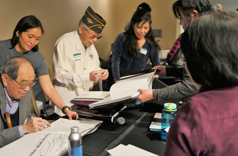 Veterans signing books for patrons