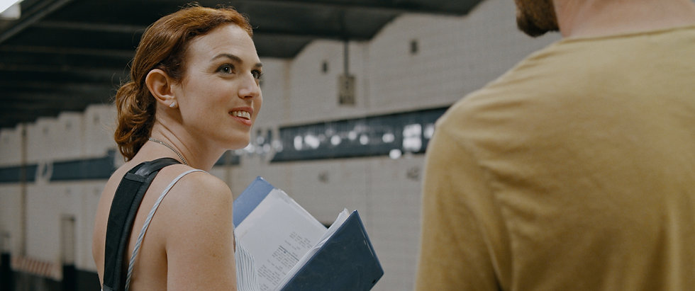 Stacey Maltin (as Chloe) holds a binder with a script in a subway station while looking up at Jay Deyonker (as Gus) in Triple Threat Film, Courtesy of Besties Make Movies, Courtesy of Besties Make Movies