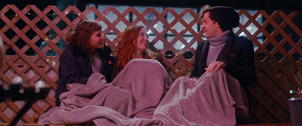 Margarita Zhitnikova, Stacey Maltin, Jay DeYonker as Maggie, Chloe and Gus sit outdoors, under a blanket with a string light decorated lattice behind them at night in Triple Threat Film, Courtesy of Besties Make Movies