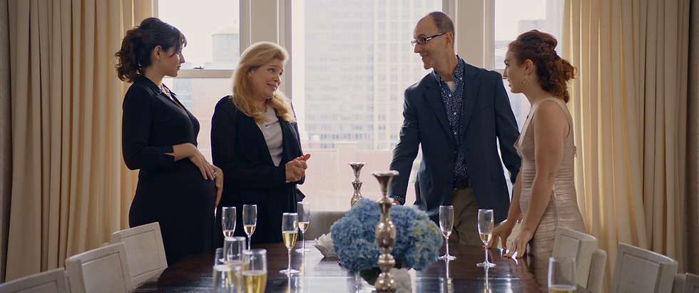 Margarita Zhitnikova (as Maggie), Catherine Curtin (as Audrey), Neal Lerner (as Brad), and Stacey Maltin (as Chloe) are dressed to the 9's and are standing around a table at an upscale apartment in Triple Threat Film, Courtesy of Besties Make Movies