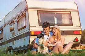 Happy couple with their dog outside a caravan
