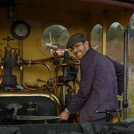 Main sitting in steam train footplate