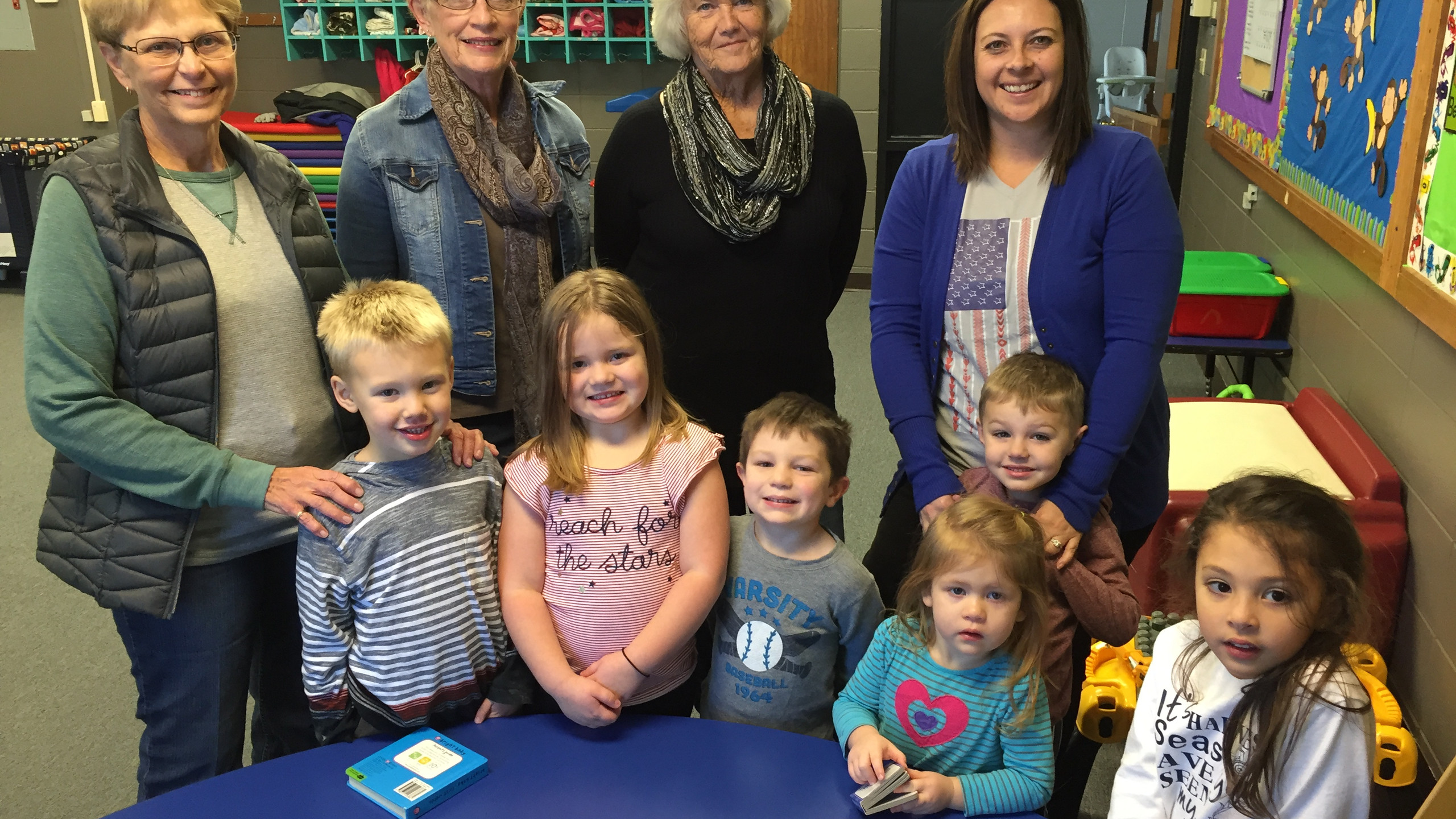 Connie Schmitz, Jeanne Applebee, and Dolly Spitzenberger of the Listen and Learn Club along with Jamie Divine, board member of the Cougar Cubs Daycare with children William Tech, Brielle Cahoy, Maddox Fuhrer, Max Divine, Bridget Cahoy, and Aubrey Piper enjoy time at the daycare.