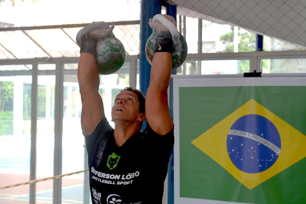Atleta em posição de Over Head ou OH lockout, exibindo a fixação consciente das peças acima da cabeça e plena estabilidade do movimento.