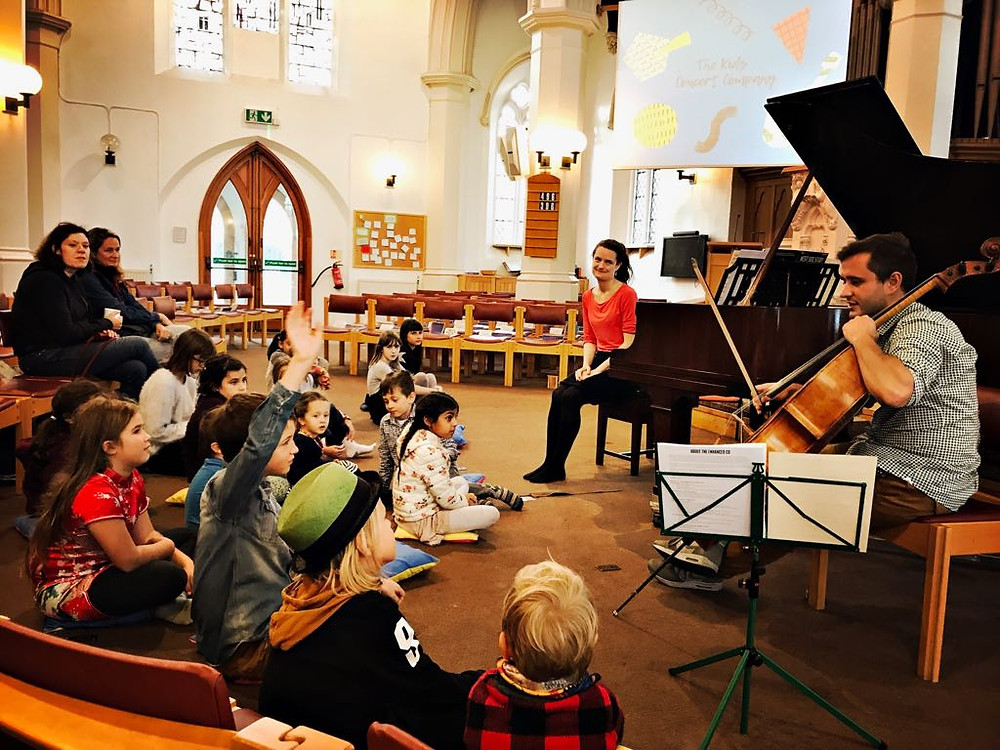 George Cooke plays the cello to the children