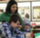 Parent and children looking at a project