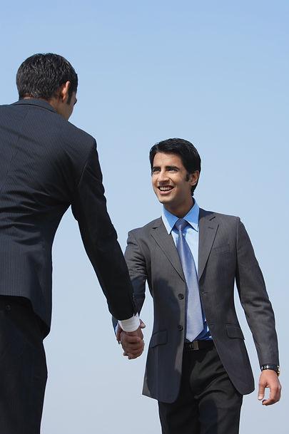 two businessmen shake hands (vertical).j