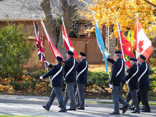 Royal Canadian Legion colour guard marches from the memorial grounds.