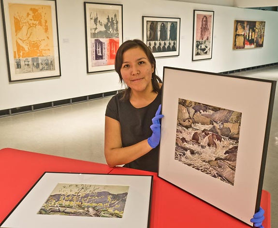 woman holding A.J Casson watercolour paintings