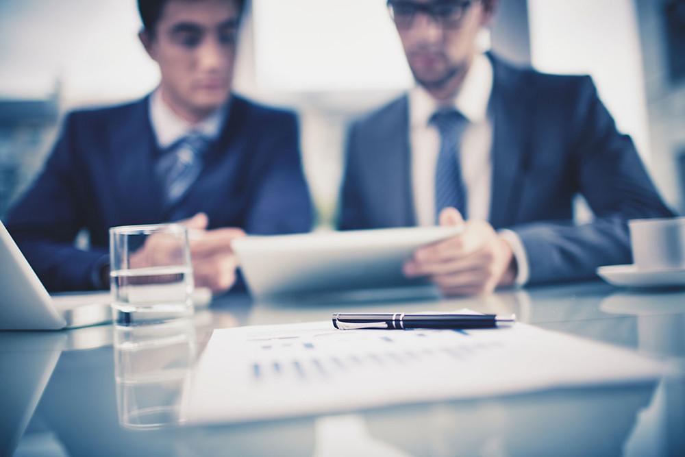 Homens conversando sobre negócios em mesa com computador
