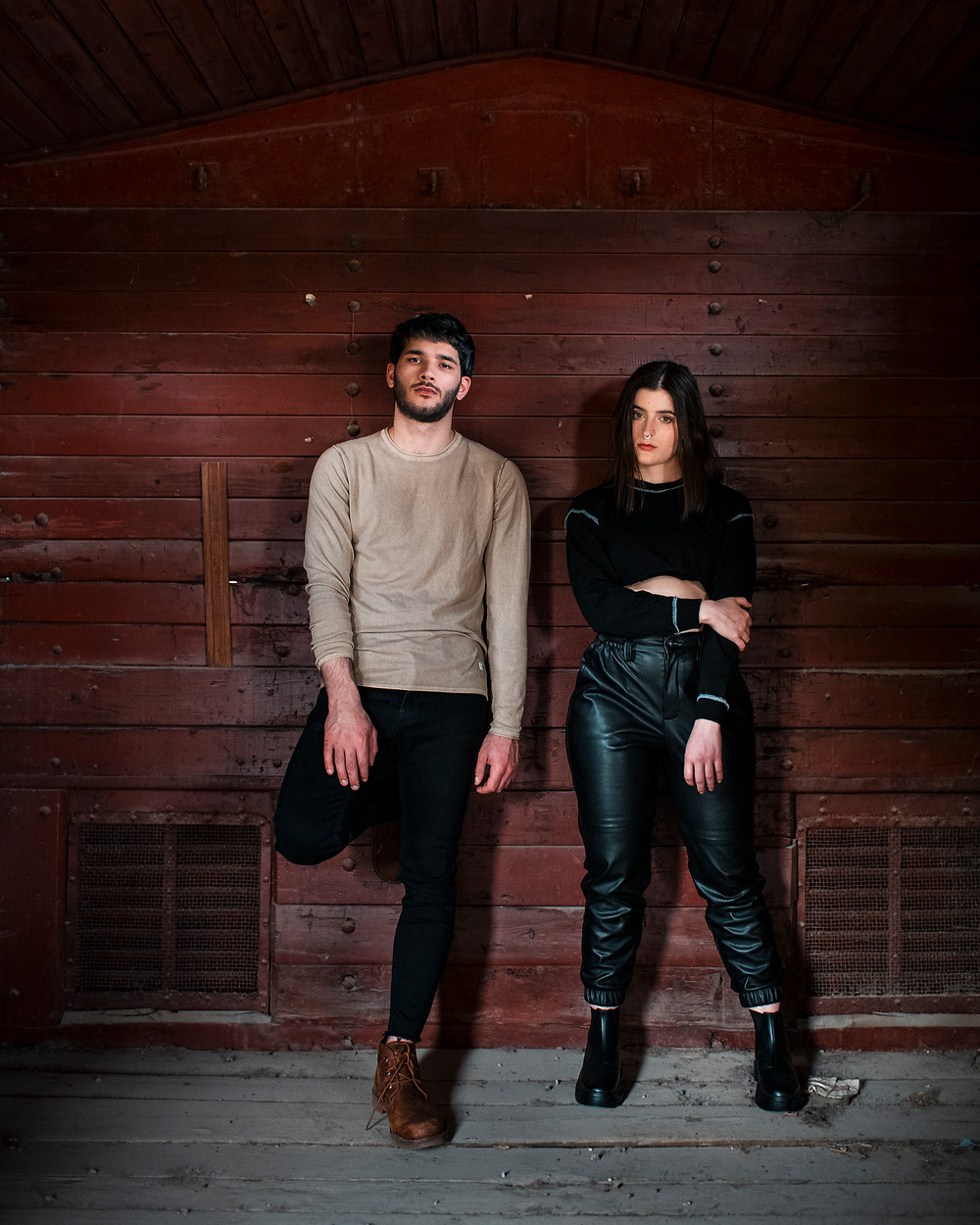 band members, man and woman leaning against wooden wall