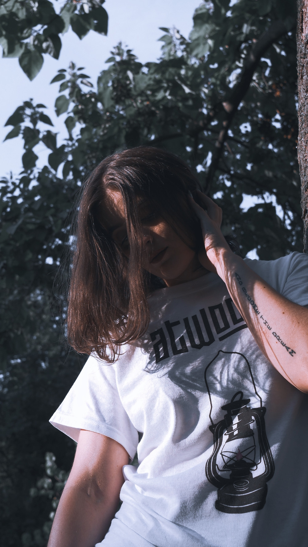 model posing whilst wearing Atwood white band t shirt with trees in background
