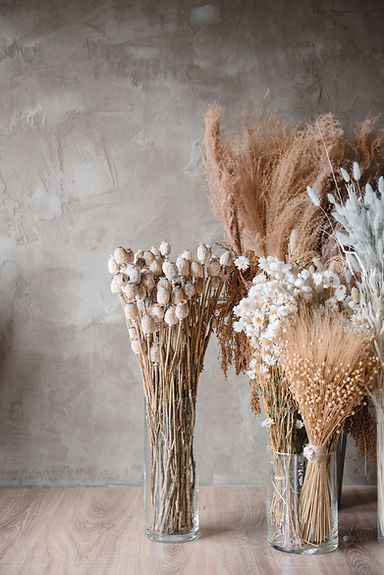 dried flowers in glass vases on the floo
