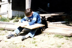 Jed Dorsey as a young artist sketching with his cat sitting next to him