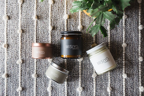 Rose Gold tin with blush pink label, Silver Tin with sage green label, Amber jar with Black label, Clear Jar with black label. Beeswax and Coconut wax candles laid down on a textured canvas.