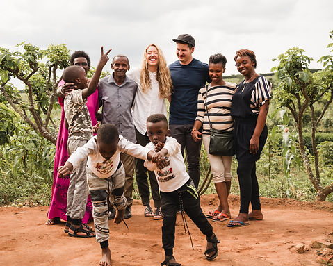 Misiyo founders visiting a family in Rwanda. Happy and smiling kids and adults are enjoying the Rwandan landscape together