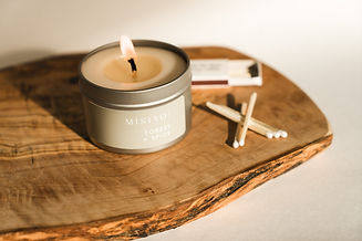 A lit silver candle tin burning. The candle is sitting on a slab of olive wood and also shows a matchbox and white-tipped matches nearby.
