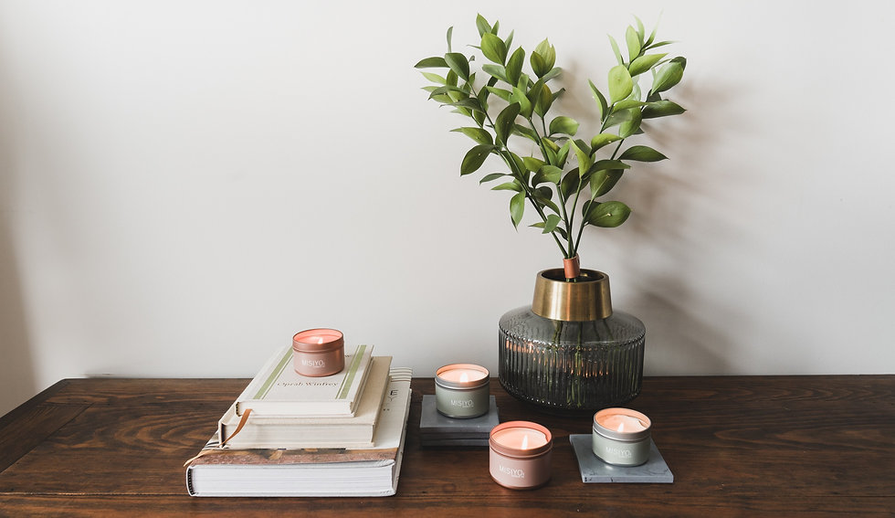 beeswax coconut wax blend candle tins along with books and greenery organized on a table in a beautiful home