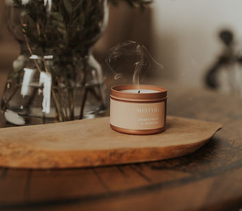 Close up of an extinguished rose gold candle tin with a small plume of white smoke. The candle is placed on a piece of wood and pictured with a vase of flowers. Grapefruit + Garden scented candle by Misiyo. Photo by Danica Matson Photography