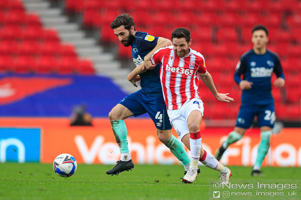 Joe Allen #4 of Stoke City and Graeme Shinnie #4 of Derby County challenge for the ball