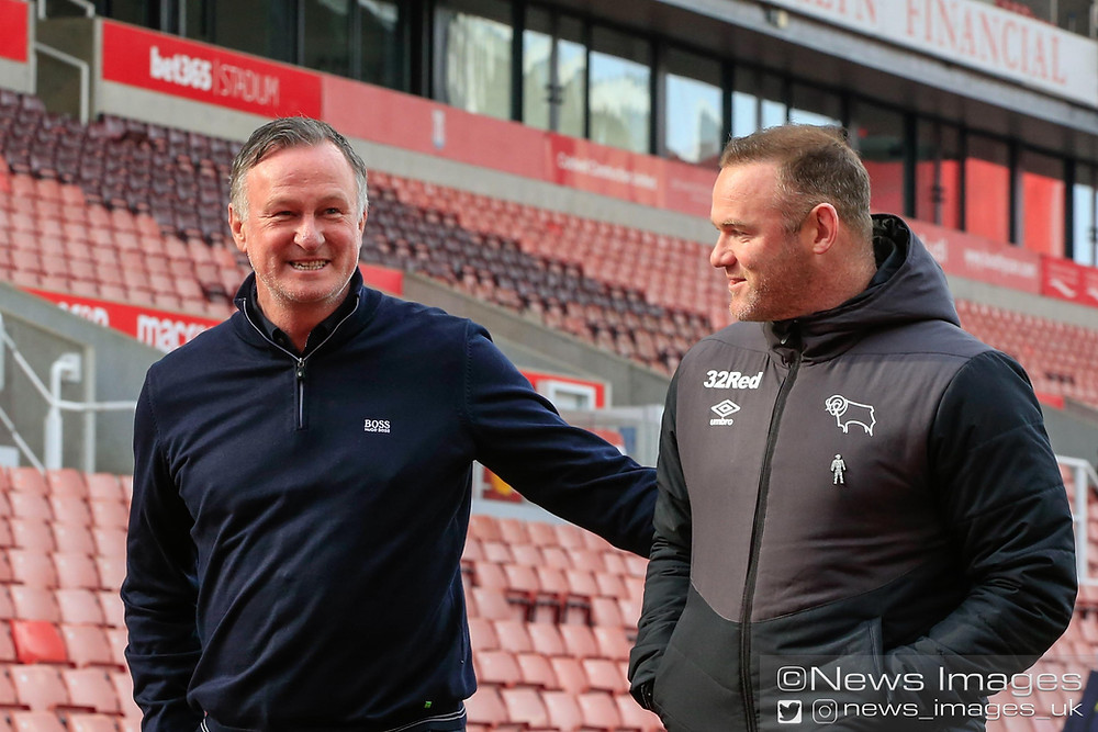 Michael O'Neill the Stoke City manager and Wayne Rooney the Derby County Manager chat before the game