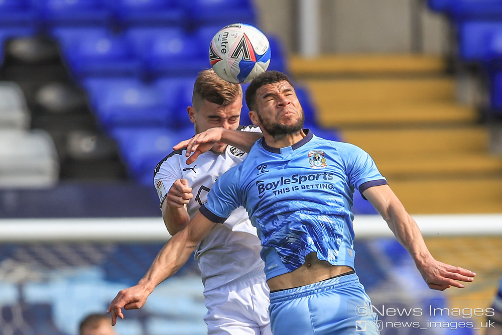 Michał Helik #30 of Barnsley and Maxime Biamou #9 of Coventry City dual for the ball