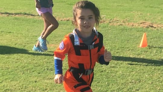 Taylor has fun running as an astronaut at Intro Run Camp.