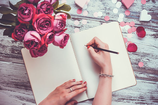 Bride writing in wedding vows notebook