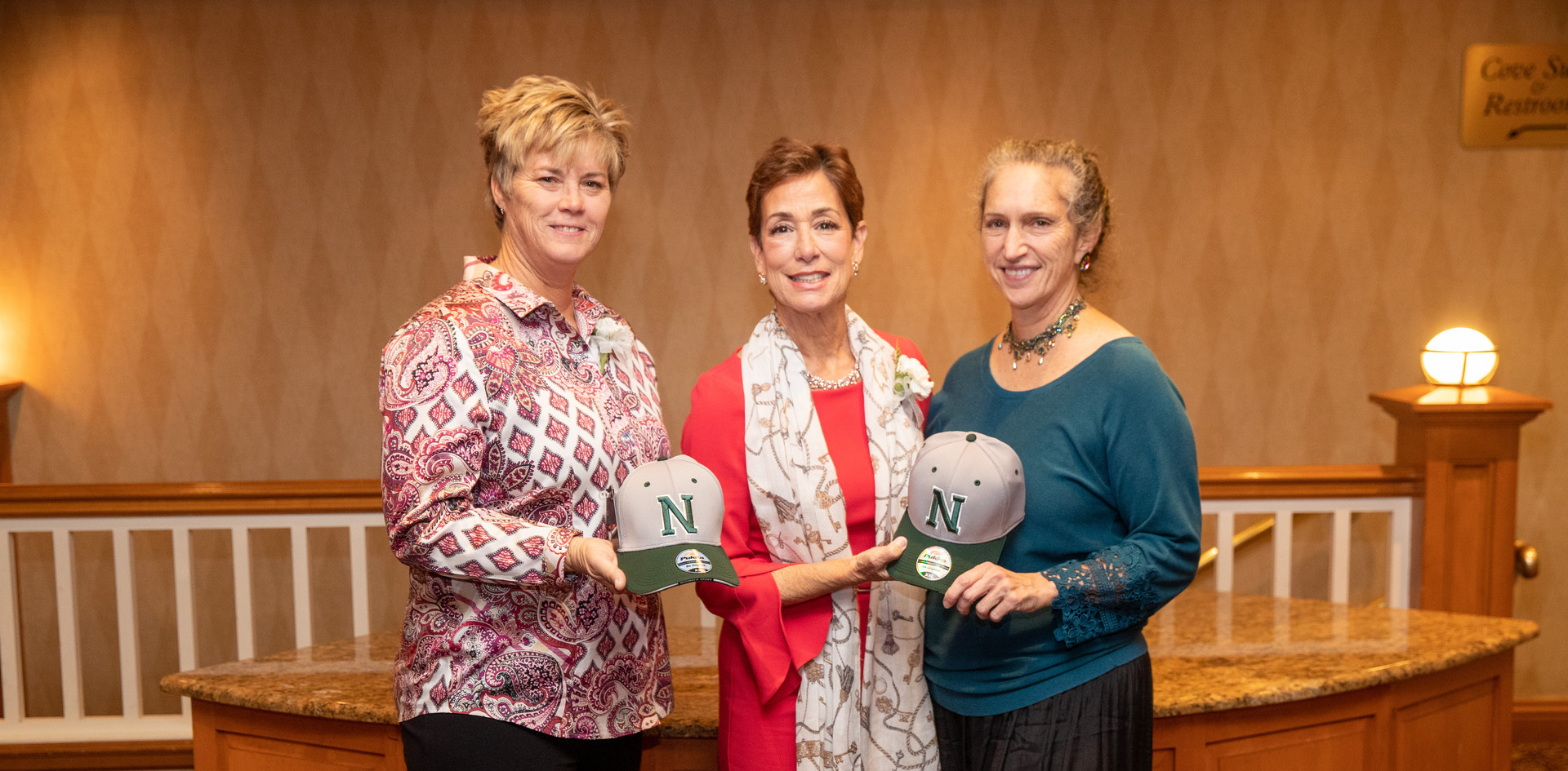 2019 honorees Missy Oman and Maria Marino with 2013 honoree Celia Bobrowsky with hats from their high school days at Norwalk High.  (photo by Josh Molaver)