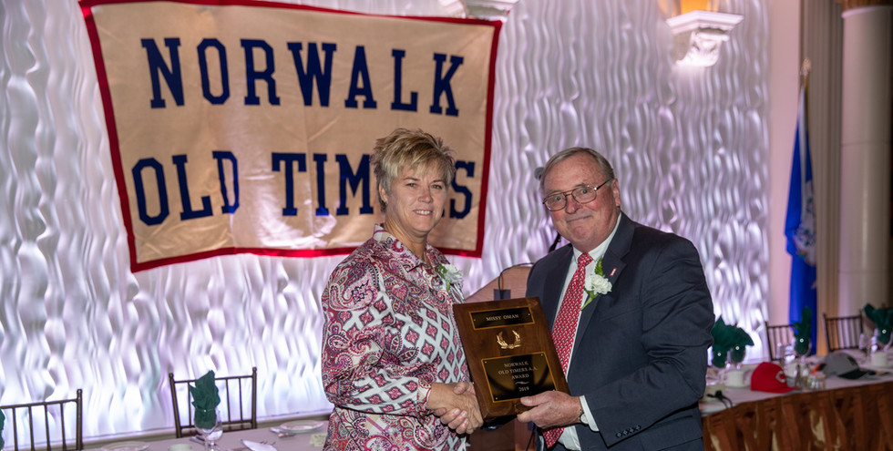 Missy Oman receives her  award-commemorating plaque from Norwalk Old Timers Association president Jack Couch.  (photo by Josh Molaver)