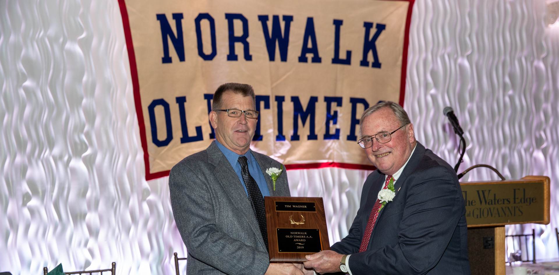 Tim Wagner receives his award-commemorating plaque from Norwalk Old Timers Association president Jack Couch.  (photo by Josh Molaver)
