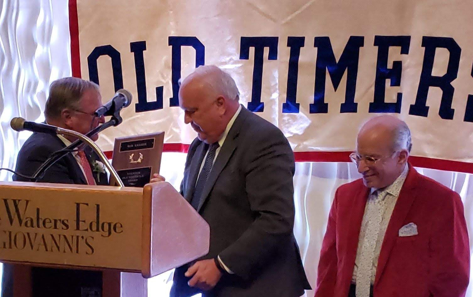 Honoree Bob Kramer receiving his plaque from Norwalk Old Timers Association president Jack Couch, with emcee George Albano far right.  (photo by Anna Mastrolillo)