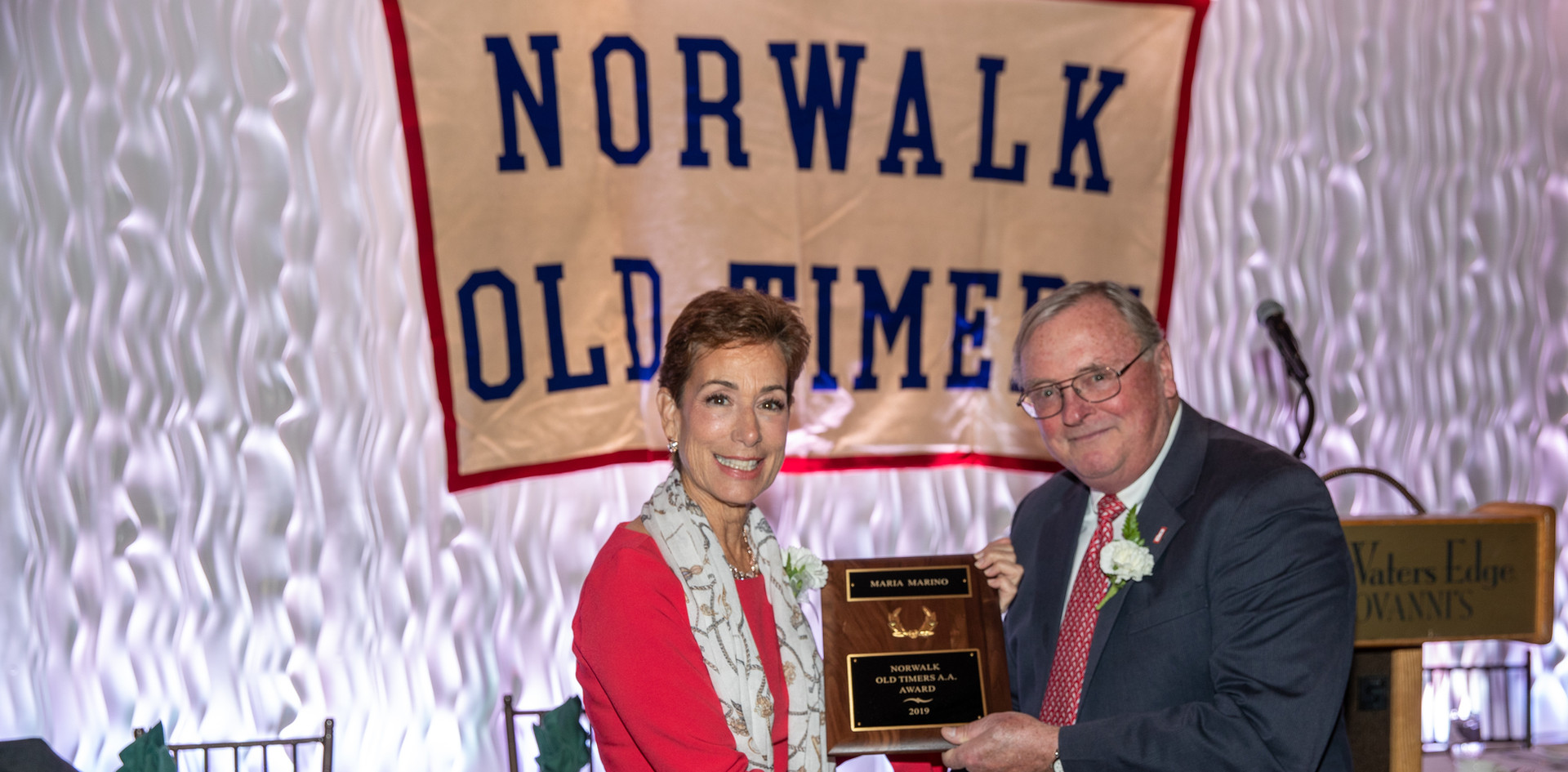 Maria Marino receives her award-commemorating plaque from Norwalk Old Timers Association president Jack Couch.  (photo by Josh Molaver)