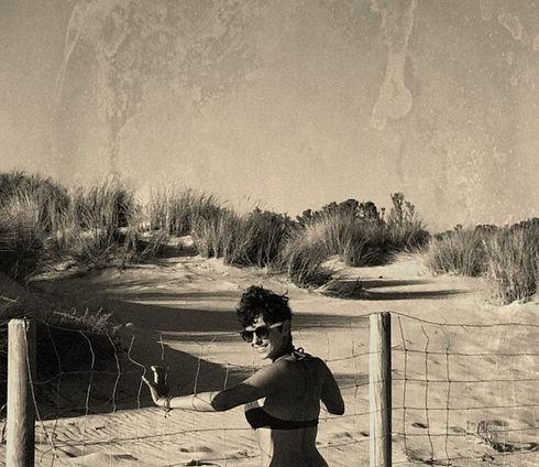 La autora sonríe en la playa.