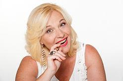 Donna bionda sorride con penna tra i denti