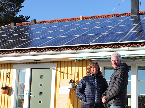 Carina och Mats framför sitt hus. På hela taket är det solpaneler.