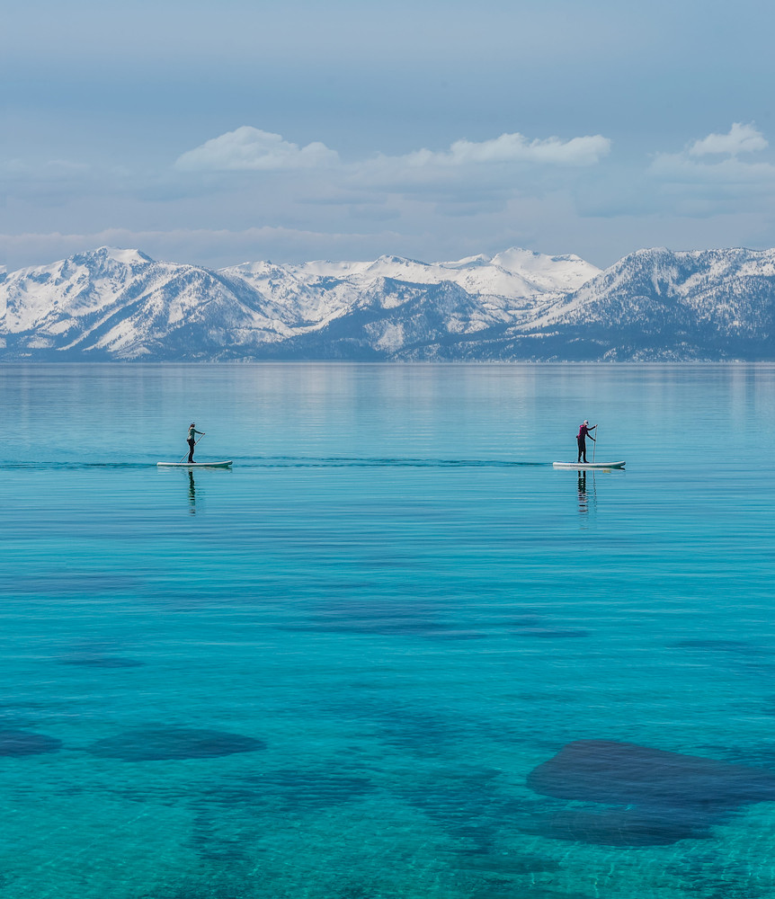 Paddle-boarders at Sand Harbor Lake Tahoe on a winter day