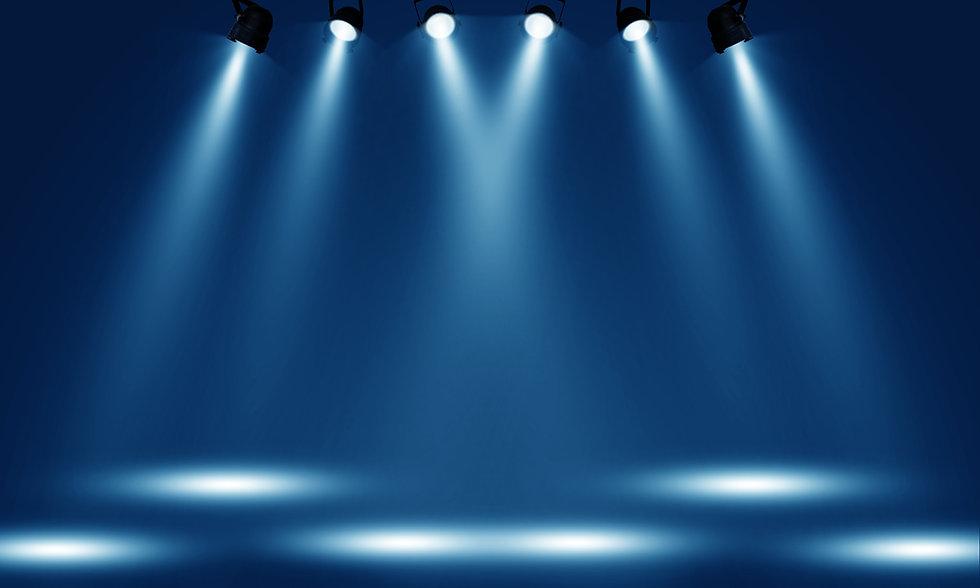 Spotlights illuminate empty stage blue background..jpg